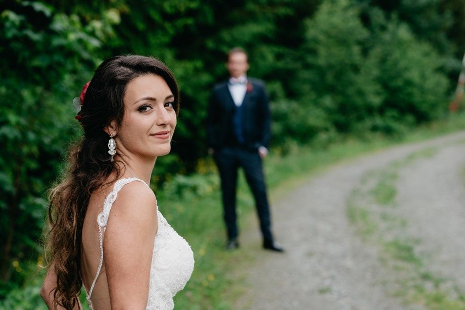 Hochzeitsfotograf: Braut mit Bräutigam im Hintergrund auf der Maierl-Alm in Kirchberg. WE WILL WEDDINGS | Hochzeitsfotografin Tirol / Wien - WE WILL WEDDINGS